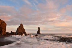 Por do sol na praia da areia do preto de Reynisfjara Imagens de Stock