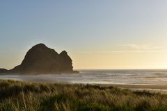 Por do sol na praia de Piha, ilha norte de Nova Zelândia imagens de stock royalty free