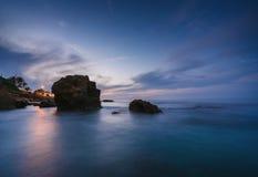 Por do sol na praia entre as rochas perto da cidade de Denia Distrito de Valência, Espanha fotografia de stock