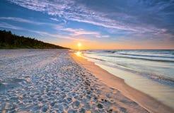 Por do sol na praia no mar Báltico fotos de stock royalty free