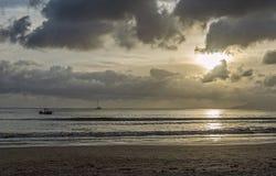 Por do sol na praia no tempo nebuloso e nos poucos barcos de pesca na água Foto de Stock