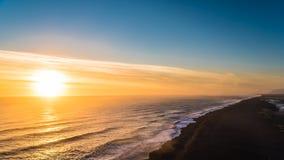 Por do sol na praia preta da areia Fotografia de Stock