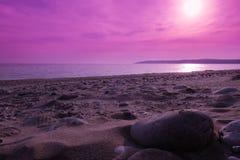 Por do sol na praia rochosa imagem de stock royalty free