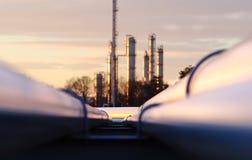 Por do sol na refinaria de petróleo bruta com rede do encanamento imagem de stock