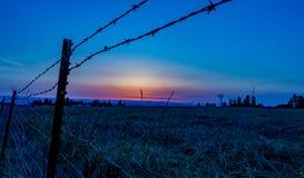 Por do sol do nanowatt através de um campo com cerca do barbwire fotografia de stock