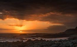 Por do sol nebuloso na costa rochosa Fotos de Stock