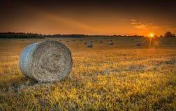Por do sol no campo montanhoso com rolos dos monte de feno imagens de stock royalty free
