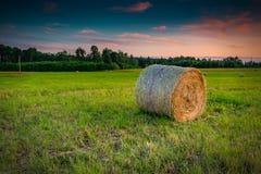 Por do sol no campo montanhoso com rolos dos monte de feno fotos de stock royalty free