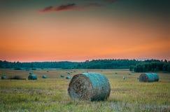 Por do sol no campo montanhoso com rolos dos monte de feno fotografia de stock