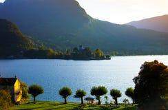 Por do sol no lago Annecy com castelo Imagens de Stock