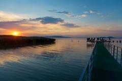 Por do sol no lago Balaton com cais e nas silhuetas em Hungria Imagem de Stock Royalty Free