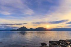 Por do sol no lago e na ilha Toya no meio fotos de stock