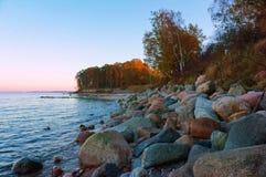 Por do sol no litoral rochoso fotos de stock