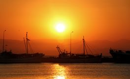 Por do sol no mar Navios no porto fotos de stock royalty free