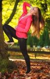 Por do sol no parque Jovem mulher completa da menina do comprimento na floresta outonal do parque Imagens de Stock