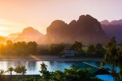 Por do sol no rio da música, Vang Vieng foto de stock