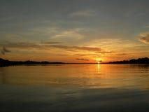 Por do sol no rio de amazon Imagens de Stock