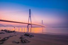 Por do sol no rio que mede a ponte Imagens de Stock