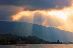 Por do sol, nuvens e montanha no lago Toba, Indonésia fotos de stock royalty free