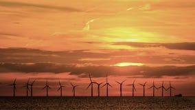 Por do sol a pouca distância do mar do vermelho alaranjado do windfarm fotos de stock