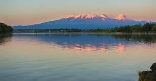 Por do sol que ilumina o grupo de Kluchevskaya de vulcões com reflexão no rio Kamchatka Imagens de Stock Royalty Free