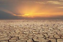 Por do sol rachado da paisagem da seca do solo Foto de Stock