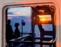 Por do sol refletido da janela na balsa Imagens de Stock