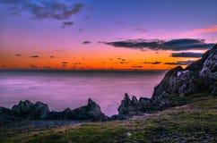 Por do sol rochoso na borda da ilha Fotos de Stock Royalty Free
