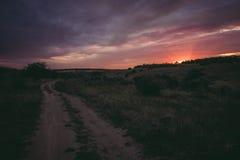 Por do sol roxo contra a estrada com campo e prado Fotografia de Stock Royalty Free