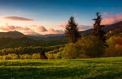 Por do sol roxo lindo no campo montanhoso imagens de stock