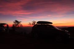 Por do sol roxo vívido espetacular e carro mostrados em silhueta Fotografia de Stock