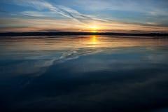 Por do sol sobre a água azul Imagens de Stock