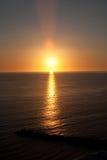 Por do sol sobre a água com ruptura da onda Fotografia de Stock