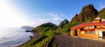 Por do sol sobre a casa de hóspedes local situada em uma baía pequena foto de stock royalty free