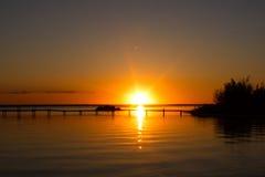Por do sol sobre a doca no lago Foto de Stock