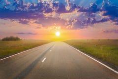 Por do sol sobre a estrada do país Imagens de Stock