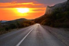 Por do sol sobre a estrada do país Imagem de Stock