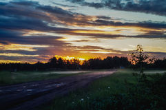 Por do sol sobre a estrada rural Foto de Stock