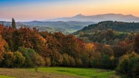 Por do sol sobre a floresta do outono em montanhas obscuras Imagens de Stock