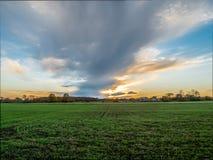 Por do sol sobre o campo de exploração agrícola rural Imagens de Stock Royalty Free