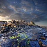 Por do sol sobre o castelo em Lindisfarne, ilha santamente, Inglaterra Fotos de Stock