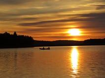Por do sol sobre o lago bonito com silhueta do barco e o céu nebuloso no fundo imagens de stock