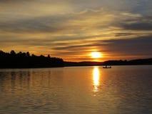 Por do sol sobre o lago bonito com silhueta do barco e o céu nebuloso no fundo imagem de stock royalty free