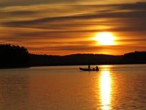 Por do sol sobre o lago bonito com silhueta do barco e o céu nebuloso no fundo imagem de stock