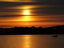 Por do sol sobre o lago bonito com silhueta do barco e o céu nebuloso no fundo foto de stock