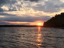 Por do sol sobre o lago com as nuvens no céu fotos de stock