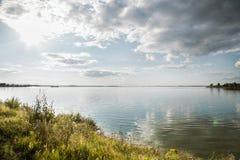 Por do sol sobre o lago na vila com nuvens de cúmulo e água calma fotos de stock royalty free