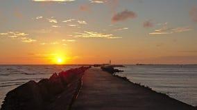 Por do sol sobre o mar Báltico com o quebra-mar na parte dianteira Imagem de Stock