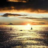 Por do sol sobre o mar com barcos imagem de stock royalty free