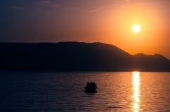 Por do sol sobre o mar e o barco com homens Foto de Stock